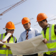 Architects at a construction site looking at blueprint — Stock Photo