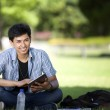 Asian male student using tablet in sunny grassland area — Stock Photo