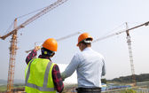 Site manager and construction worker checking plans — Stock Photo