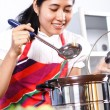 Asian woman tasting her cooking — Foto de Stock