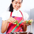 Young woman making salad in the kitchen — Stock Photo