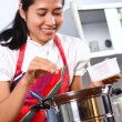 Stock Photo: Young woman cooking in the kitchen