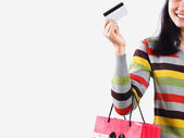Shopping woman with bag and a credit card over white background — Stock fotografie