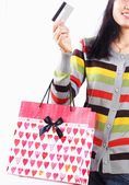 Shopping woman with bag and a credit card over white background — Stock Photo