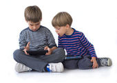 Two brothers playing games on the tablets — Stockfoto