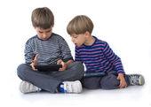 2 人の兄弟、タブレット上のゲームをプレイ — ストック写真