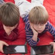 Boys playing video games on tablets — Stock Photo