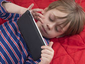 Kid playing video game on tablet computer — Stock Photo