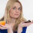 Woman with healthy oranges in one hand and chocolate in another — Stock Photo