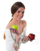 Beautiful young woman with fresh apples and measuring tape — Stock Photo