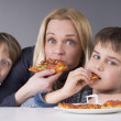 Hungry family, mother and son eating pizza, younger kid prefers strawberries — Stock Photo