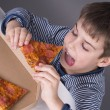 Boy enjoys eating pizza — Stock Photo