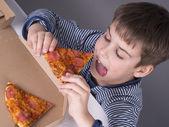 Boy enjoys eating pizza — Stock Photo