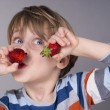 Cute kid eating strawberries — Stock Photo