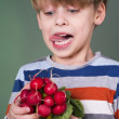 Beautiful boy likes radish and salad — Stock Photo