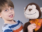 Lovely kid giving pizza to his monkey doll — Stock Photo