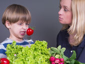 Mother trying to feed her little son who hates eating tomato — Stock Photo
