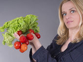 Pretty woman holding green salad and vegetables, good for diet — Stock Photo