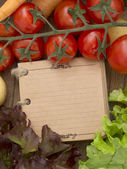 Vegetables on the wooden background with notebook — Stock Photo
