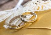 Wedding rings on the yellow silk — Stock Photo