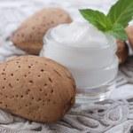 Facial cream and almonds — Stock Photo