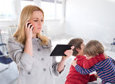 Busy mother with tablet and mobile while her children fighting — Stock Photo