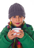 Beautiful schoolboy in winter clothes, drinking a tea — Stock Photo