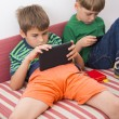 Schoolboys playing video games on table computers — Stockfoto