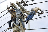 Team work electrician men on electric poles. — Stock Photo