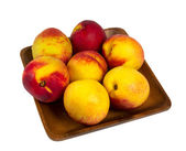 Nectarines in wooden plate — Stock Photo