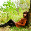 Woman sitting near a tree — Foto Stock