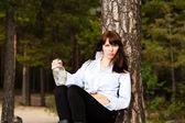 Frau sitzt in einem baum — Stockfoto