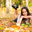 Stock Photo: Beautiful womlying on autumn leaves