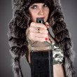 Woman in a fur hat holds out a bottle — Stock Photo