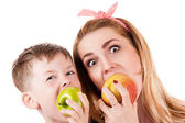 Mother son cheerfully biting apple — Stock Photo