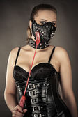 Woman in corset and mask with spikes — Stock Photo