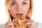 Woman closeup eating a hamburger — Stock Photo