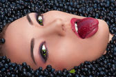 Woman lying in blueberries shows colored tongue — Stock Photo