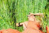 Woman in orange dress lying on the immature wheat — Stock Photo