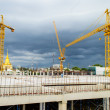 Foto Stock: Construction site with crane near building on Cloudy storm backg