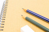Två trä blyertspenna och radergummi på återvinna anteckningsbok på vit bakgrund. — Stockfoto