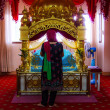A Woman Sikh pilgrims stand praying in room at Gurdwara Siri Guru Singh Sabha. - Stock Photo
