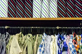 Colorful collection of men's clothes hanging on a rack and Color — Stock Photo