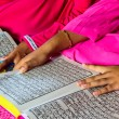 A Young Muslim Girl reading the Holy Quran. - Stock Photo