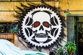 Street Art Graffiti Face Skull in Ratchet on wall. — Stock Photo