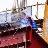 A Construction Worker welding steel bars on construction site. — Stock Photo