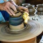 Potter makes on the pottery wheel clay pot. — Stock Photo #30277319
