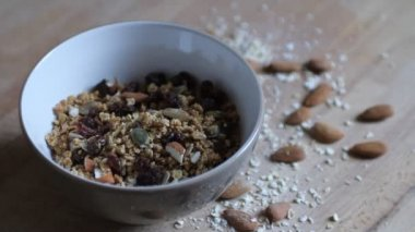 Pouring milk in a bowl with granola — Stock Video