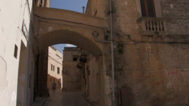 Old woman walking through narrow road — Stock Video