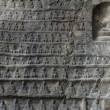 wall of miniature buddhas carved in stone — Stock Photo